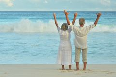 Elderly couple running  on beach. Happy elderly couple on sandy beach near tropical resort with open arms Stock Photography