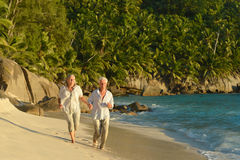 Elderly couple running on the beach Royalty Free Stock Photo
