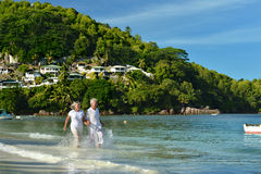Elderly couple running on the beach Stock Image