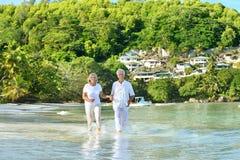 Elderly couple running on the beach Stock Photos