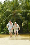 Elderly couple running on the beach Stock Images