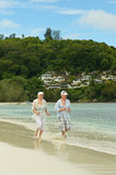 Elderly couple running on the beach Stock Photo