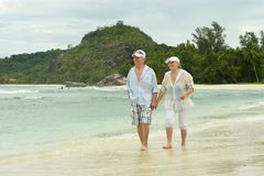 Elderly couple running  on beach Stock Image