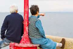 Elderly Couple at the Seaside. An elderly couple watch and point to sea from on shore at a red light post royalty free stock photography