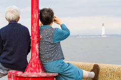 Elderly Couple at the Seaside. An elderly couple watch a yacht from on shore at a red light post stock photo