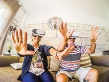 Elderly couple senior play with virtual reality headset. Couple of senior playing at roller coaster with virtual reality headset sitting on the sofa at home stock photography
