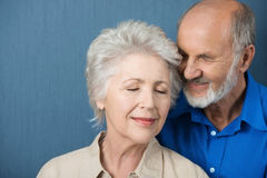 Elderly couple share a tender moment. Of love as they stand close together with their eyes closed in contentment and bliss royalty free stock images