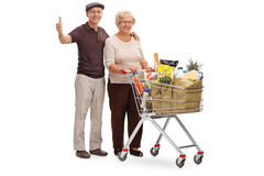 Elderly couple with shopping cart and thumb up Stock Photo
