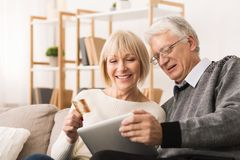 Elderly couple shopping online with tablet and credit card. At home royalty free stock photography