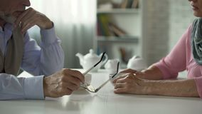 Elderly couple sitting across table over cup of tea, tensed relationship, crisis stock footage
