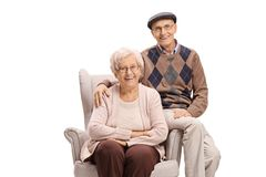 Elderly couple sitting in an armchair and looking at the camera. Isolated on white background stock image