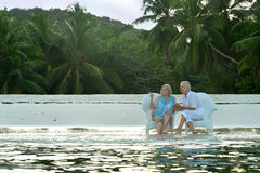 Elderly couple sitting on a background of palm trees Stock Photo