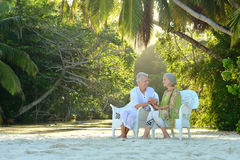 Elderly couple sitting on a beach Stock Images