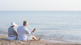 elderly couple sitting on a beach stock video footage