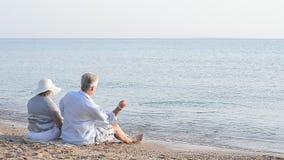 Elderly couple sitting on a beach. Happy elderly couple sitting on a sandy beach near the sea stock video footage