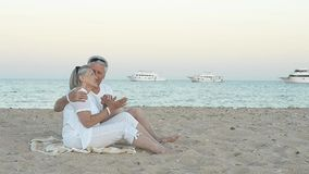 Elderly couple sitting on a beach. Happy elderly couple sitting on a sandy beach near the sea stock video
