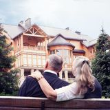 Elderly couple sitting on bench in garden near house. Royalty Free Stock Image