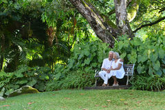 Elderly couple sitting on a bench outdoors Stock Photo