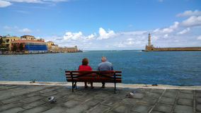 An elderly couple sitting on a bench on the promenade and admire the views in the center of Chania stock photography