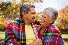 Elderly couple sitting on bench smiling at each other with a blanket Stock Image