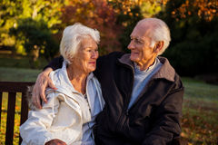 Elderly couple sitting on bench smiling at each other in park Stock Photography