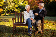 Elderly couple sitting on bench smiling at each other in park royalty free stock photography