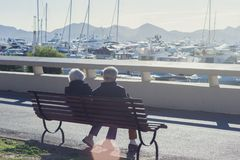 An elderly couple is sitting on a bench among white expensive yachts and mountains on a sunny day. royalty free stock photo