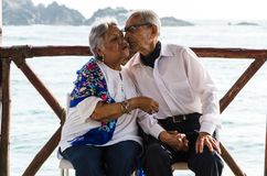 Elderly couple sitting on chairs kissing stock photography