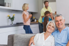 Elderly couple sitting on the couch and smiling at camera Stock Images