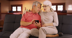 Elderly couple sitting on couch using smartphone Royalty Free Stock Images
