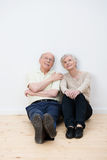Elderly couple sitting daydreaming in a new home. Elderly couple sitting daydreaming on the bare wooden floor in their living room in their new home Stock Photography