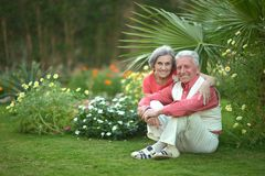 Elderly couple sitting on grass Stock Images