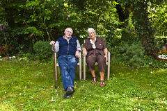 Elderly couple sitting hand in hand Royalty Free Stock Image