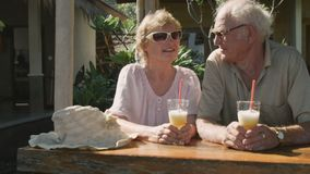 Elderly couple sitting in outdoors cafe with cocktails stock footage