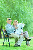Elderly couple sitting in park and reading the news. Happy elderly couple sitting in park and reading the news Royalty Free Stock Photo