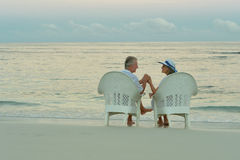 Elderly couple sitting on the shore Stock Image