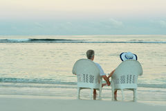 Elderly couple sitting on the shore Stock Photos