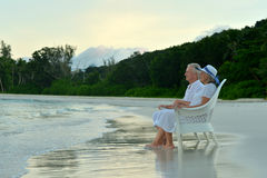 Elderly couple sitting on the shore Royalty Free Stock Image