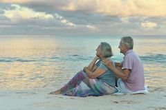 Elderly couple sitting on the shore Royalty Free Stock Photography