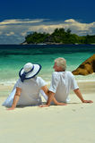 Elderly couple sitting on the shore Stock Photography