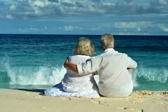 Elderly couple sitting on the shore Stock Photo