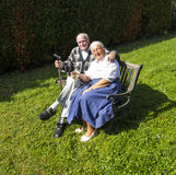 Elderly couple sitting in their garden on a bench Stock Image