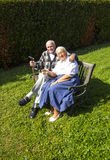 Elderly couple sitting in their garden on a bench Stock Images