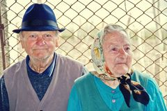 Elderly couple sitting together on a country road Stock Photo