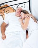 Elderly couple sleeping in bed. Royalty Free Stock Images