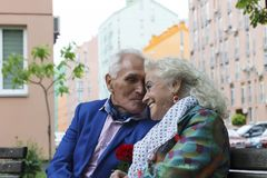 Elderly couple smiling and talking while sitting on a park bench. stock images