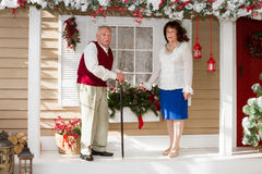 Elderly couple. Standing near the porch decorated home Stock Images