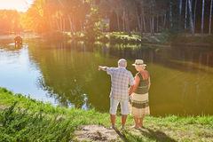 Elderly couple standing near water. People admiring the view, park Stock Images