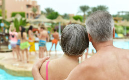 Elderly couple standing by pool Stock Photos