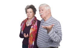 Elderly couple standing with questioning expressions Stock Photo